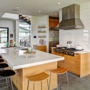 Contemporary kitchen designs - Example of a trendy concrete floor and gray floor kitchen design in Salt Lake City with an undermount sink, flat-panel cabinets, light wood cabinets, white backsplash, porcelain backsplash, stainless steel appliances, an island and white countertops