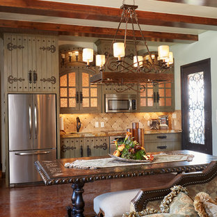 Design ideas for a mid-sized mediterranean l-shaped eat-in kitchen in Dallas with an undermount sink, glass-front cabinets, beige cabinets, granite benchtops, beige splashback, ceramic splashback, stainless steel appliances, concrete floors and no island.