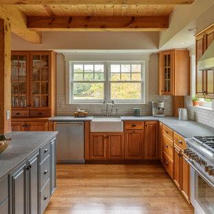Bild på ett stort vintage grå grått l-kök, med luckor med upphöjd panel, skåp i mellenmörkt trä, vitt stänkskydd, stänkskydd i tunnelbanekakel, rostfria vitvaror, en köksö och brunt golv
