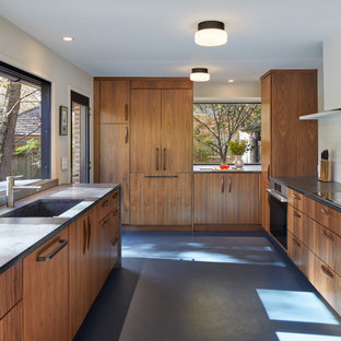 Inspiration for a midcentury kitchen in DC Metro with an integrated sink, flat-panel cabinets, medium wood cabinets, soapstone benchtops, white splashback, ceramic splashback, stainless steel appliances, linoleum floors, blue floor and grey benchtop.