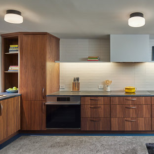 Design ideas for a midcentury kitchen in DC Metro with an integrated sink, flat-panel cabinets, medium wood cabinets, soapstone benchtops, white splashback, ceramic splashback, stainless steel appliances, linoleum floors, blue floor and grey benchtop.