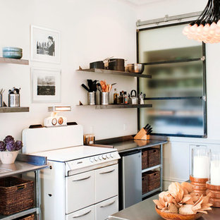 Inspiration for a mid-sized contemporary single-wall dark wood floor enclosed kitchen remodel in San Francisco with open cabinets, white appliances, an undermount sink, stainless steel cabinets, stainless steel countertops, white backsplash and an island