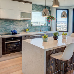 Inspiration for a mid-sized modern l-shaped eat-in kitchen in San Francisco with an undermount sink, flat-panel cabinets, white cabinets, solid surface benchtops, green splashback, glass tile splashback, light hardwood floors, with island, beige floor and beige benchtop.
