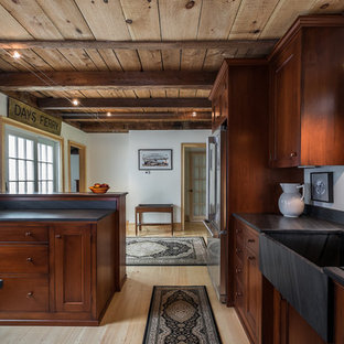 Small farmhouse enclosed kitchen pictures - Example of a small cottage l-shaped light wood floor enclosed kitchen design in Portland Maine with a farmhouse sink, stainless steel appliances, a peninsula, recessed-panel cabinets, dark wood cabinets, soapstone countertops and red backsplash