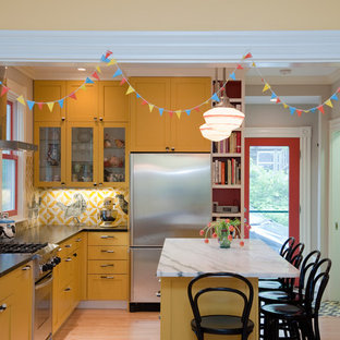 Mid-sized eclectic l-shaped enclosed kitchen photo in Boston with an undermount sink, shaker cabinets, yellow cabinets, soapstone countertops and stainless steel appliances