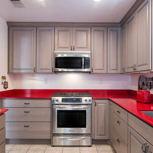 This is an example of a small modern u-shaped eat-in kitchen in San Diego with an undermount sink, raised-panel cabinets, grey cabinets, quartz benchtops, stainless steel appliances, ceramic floors, no island and red benchtop.