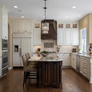 Idéer för ett stort klassiskt flerfärgad kök, med vita skåp, beige stänkskydd, rostfria vitvaror, en köksö, brunt golv, en undermonterad diskho, luckor med upphöjd panel, bänkskiva i kvarts, stänkskydd i stenkakel och mellanmörkt trägolv