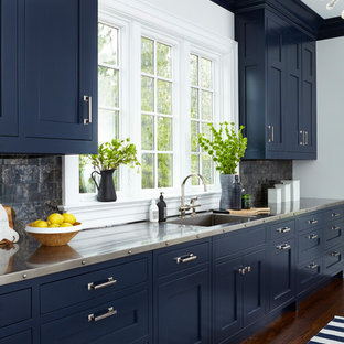 Einzeilige, Mittelgroße Moderne Küche mit Unterbauwaschbecken, Schrankfronten im Shaker-Stil, blauen Schränken, Edelstahl-Arbeitsplatte, Küchenrückwand in Schwarz, dunklem Holzboden und braunem Boden in New York