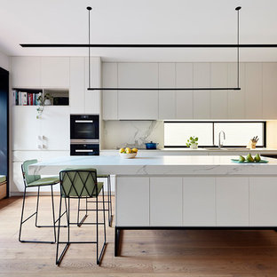 Design ideas for a contemporary galley kitchen in Melbourne with an undermount sink, louvered cabinets, white cabinets, white splashback, medium hardwood floors, with island, brown floor and white benchtop.