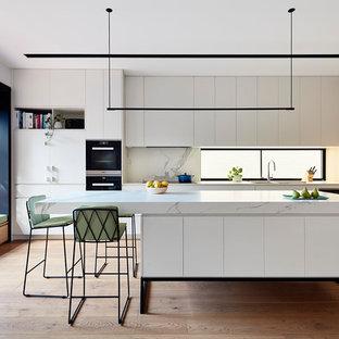 Cette photo montre une cuisine parallèle tendance avec un évier encastré, un placard à porte persienne, des portes de placard blanches, une crédence blanche, un sol en bois brun, un îlot central, un sol marron et un plan de travail blanc.