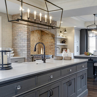 Large country galley eat-in kitchen in Columbus with an undermount sink, beaded inset cabinets, grey cabinets, quartz benchtops, brick splashback, dark hardwood floors and multiple islands.