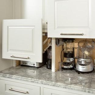 Ejemplo de cocina en U, tradicional, extra grande, con fregadero sobremueble, armarios con rebordes decorativos, puertas de armario blancas, encimera de granito, suelo de madera oscura y una isla