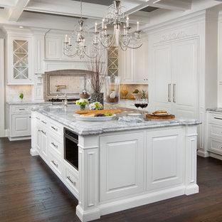 Свежая идея для дизайна: огромная п-образная кухня в классическом стиле с фасадами с декоративным кантом, белыми фасадами, белым фартуком, техникой под мебельный фасад, темным паркетным полом, островом, столешницей из гранита и фартуком из каменной плитки - отличное фото интерьера