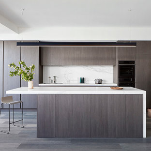 Small contemporary single-wall open plan kitchen in Melbourne with flat-panel cabinets, dark wood cabinets, white splashback, stone slab splashback, dark hardwood floors, with island and brown floor.