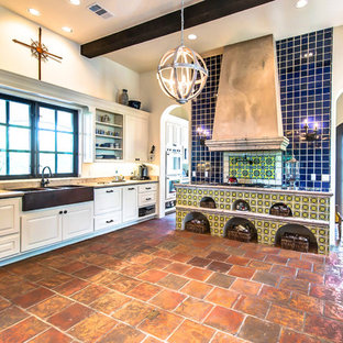 Photo of a mid-sized country galley eat-in kitchen in Austin with a farmhouse sink, limestone benchtops, blue splashback, terra-cotta splashback, terra-cotta floors and no island.