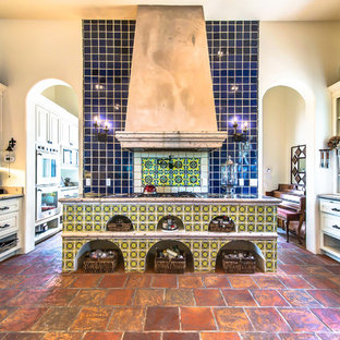 Inspiration for a mid-sized galley eat-in kitchen in Austin with a farmhouse sink, limestone benchtops, blue splashback, terra-cotta splashback, terra-cotta floors and no island.