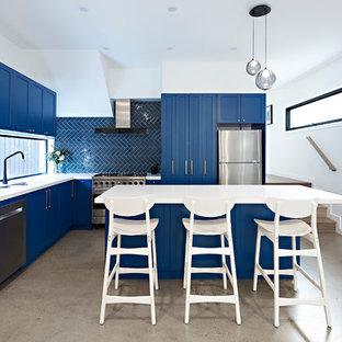 Mid-sized transitional l-shaped kitchen in Melbourne with a double-bowl sink, shaker cabinets, blue cabinets, blue splashback, stainless steel appliances, with island, white benchtop, ceramic splashback, concrete floors, grey floor and quartz benchtops.