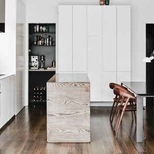 This is an example of a contemporary l-shaped eat-in kitchen in Melbourne with flat-panel cabinets, white cabinets, white splashback, dark hardwood floors, with island, brown floor and white benchtop.