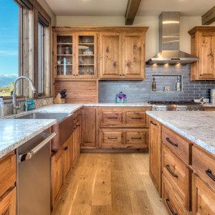 Rustikale Küche in L-Form mit Landhausspüle, profilierten Schrankfronten, hellbraunen Holzschränken, Küchenrückwand in Grau, Rückwand aus Metrofliesen, Küchengeräten aus Edelstahl, hellem Holzboden, Kücheninsel, beigem Boden und grauer Arbeitsplatte in Sonstige