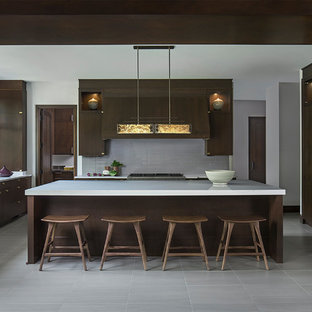 This is an example of a mid-sized contemporary eat-in kitchen in Detroit with a drop-in sink, dark wood cabinets, quartz benchtops, green splashback, glass tile splashback, panelled appliances, ceramic floors, with island, grey floor and flat-panel cabinets.