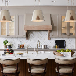 Photo of a large transitional kitchen in Minneapolis with quartz benchtops, with island, white benchtop, marble splashback, an integrated sink, glass-front cabinets, beige cabinets, multi-coloured splashback and light hardwood floors.