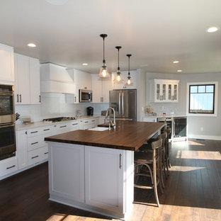 Mittelgroße Klassische Wohnküche in L-Form mit Landhausspüle, weißen Schränken, Marmor-Arbeitsplatte, Küchenrückwand in Weiß, Rückwand aus Porzellanfliesen, Küchengeräten aus Edelstahl, dunklem Holzboden, Kücheninsel, Schrankfronten im Shaker-Stil und braunem Boden in Kansas City