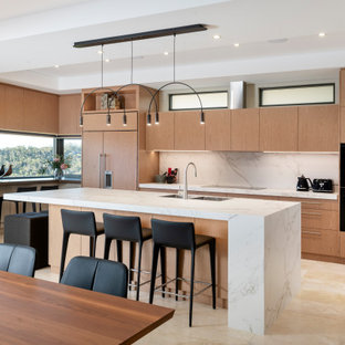 Large contemporary l-shaped open plan kitchen in Perth with a double-bowl sink, recessed-panel cabinets, light wood cabinets, white splashback, black appliances, travertine floors, with island, beige floor and white benchtop.