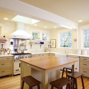 Traditional kitchen remodeling - Kitchen - traditional l-shaped kitchen idea in Boston with a farmhouse sink, raised-panel cabinets, beige cabinets, wood countertops, white backsplash and white appliances