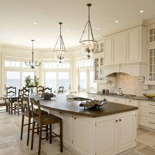 На фото: кухни в классическом стиле с обеденным столом, фасадами с выступающей филенкой, белыми фасадами, фартуком из известняка и коричневой столешницей