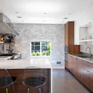 Inspiration for a mid-sized contemporary l-shaped eat-in kitchen in Seattle with an integrated sink, flat-panel cabinets, dark wood cabinets, quartz benchtops, stone tile splashback, panelled appliances, grey splashback, linoleum floors, a peninsula and grey floor.