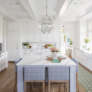 Design ideas for a large transitional u-shaped open plan kitchen in Minneapolis with a farmhouse sink, recessed-panel cabinets, white cabinets, quartz benchtops, white splashback, subway tile splashback, panelled appliances, medium hardwood floors, with island, brown floor, white benchtop and coffered.