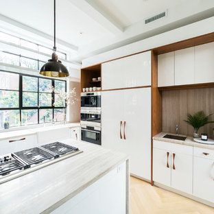 Mid-sized contemporary kitchen pictures - Example of a mid-sized trendy u-shaped light wood floor and beige floor kitchen design in New York with a drop-in sink, flat-panel cabinets, white cabinets, beige backsplash, stainless steel appliances, an island and beige countertops