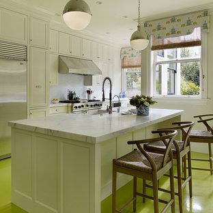 На фото: кухня в современном стиле с техникой из нержавеющей стали, деревянным полом и зеленым полом с