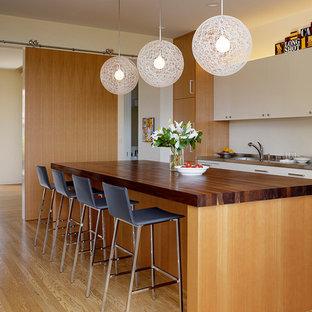 サンフランシスコの大きいコンテンポラリースタイルのおしゃれなキッチン (フラットパネル扉のキャビネット、中間色木目調キャビネット、木材カウンター、無垢フローリング、一体型シンク、パネルと同色の調理設備) の写真