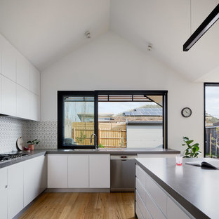 Large contemporary u-shaped open plan kitchen in Melbourne with flat-panel cabinets, white cabinets, quartz benchtops, ceramic splashback, stainless steel appliances, with island, grey benchtop, a drop-in sink, multi-coloured splashback, medium hardwood floors and beige floor.