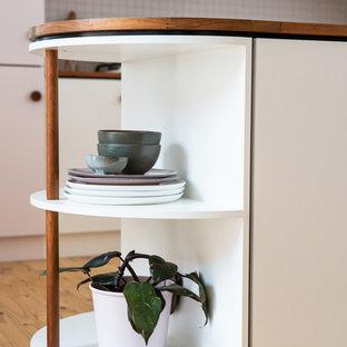 Small midcentury u-shaped open plan kitchen in Adelaide with flat-panel cabinets, laminate benchtops, white splashback, ceramic splashback, white appliances and light hardwood floors.