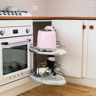 Design ideas for a small midcentury u-shaped open plan kitchen in Adelaide with flat-panel cabinets, laminate benchtops, white splashback, ceramic splashback, white appliances and light hardwood floors.