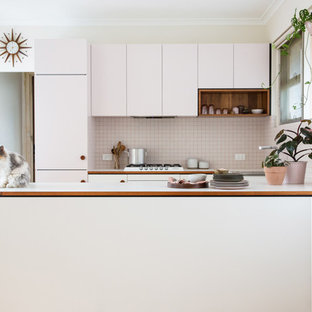 This is an example of a small midcentury u-shaped open plan kitchen in Adelaide with flat-panel cabinets, laminate benchtops, white splashback, ceramic splashback, white appliances and light hardwood floors.