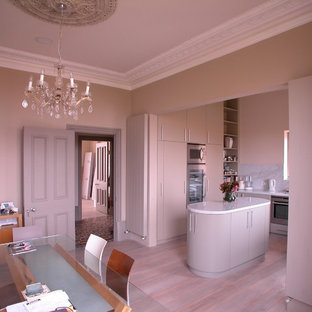 Design ideas for a small traditional u-shaped eat-in kitchen in London with an undermount sink, flat-panel cabinets, red cabinets, quartzite benchtops, white splashback, marble splashback, stainless steel appliances, light hardwood floors, with island and beige floor.