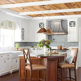 Modelo de cocina comedor en L, rústica, grande, con fregadero sobremueble, puertas de armario blancas, salpicadero azul, salpicadero con mosaicos de azulejos, suelo de madera oscura y una isla