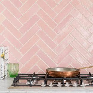 Inredning av ett vit vitt kök och matrum, med marmorbänkskiva, rosa stänkskydd och stänkskydd i keramik