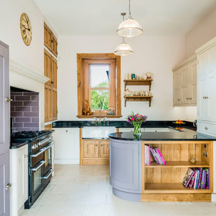 Medium sized traditional u-shaped kitchen in Other with a belfast sink, granite worktops, black appliances, shaker cabinets, purple cabinets, window splashback, a breakfast bar and white floors.