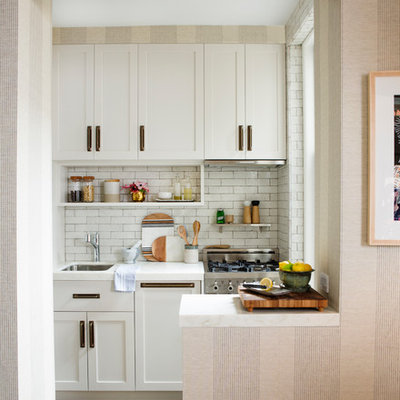 Eat-in kitchen - small contemporary l-shaped light wood floor and beige floor eat-in kitchen idea in New York with an undermount sink, shaker cabinets, white cabinets, marble countertops, white backsplash, subway tile backsplash, stainless steel appliances and a peninsula