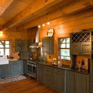 Inspiration for a mid-sized country l-shaped open plan kitchen in Charlotte with a drop-in sink, recessed-panel cabinets, green cabinets, granite benchtops, black splashback, stainless steel appliances, medium hardwood floors and no island.