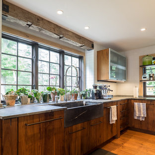 This is an example of a mid-sized country galley separate kitchen in Philadelphia with a farmhouse sink, open cabinets, medium wood cabinets, soapstone benchtops, white splashback, stainless steel appliances, medium hardwood floors, with island, brown floor and glass tile splashback.