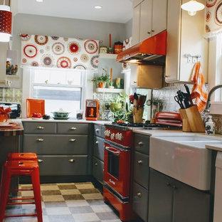 ポートランドの小さいエクレクティックスタイルのおしゃれなコの字型キッチン (フラットパネル扉のキャビネット、白いキャビネット、アイランドなし、珪岩カウンター、エプロンフロントシンク、カラー調理設備、黒い床) の写真