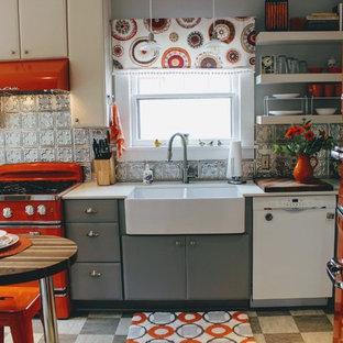 ポートランドの小さいエクレクティックスタイルのおしゃれなコの字型キッチン (エプロンフロントシンク、フラットパネル扉のキャビネット、白いキャビネット、珪岩カウンター、カラー調理設備、アイランドなし、黒い床) の写真