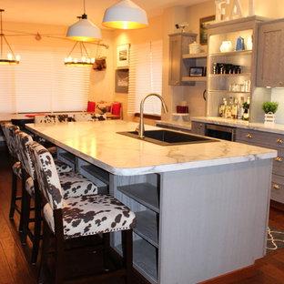 シアトルの中サイズのインダストリアルスタイルのおしゃれなキッチン (エプロンフロントシンク、シェーカースタイル扉のキャビネット、グレーのキャビネット、ラミネートカウンター、白いキッチンパネル、セラミックタイルのキッチンパネル、シルバーの調理設備の、濃色無垢フローリング、茶色い床) の写真
