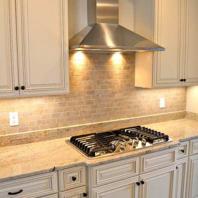 Inspiration for a mid-sized transitional u-shaped medium tone wood floor enclosed kitchen remodel in Boston with an undermount sink, raised-panel cabinets, white cabinets, granite countertops, beige backsplash, stone tile backsplash, stainless steel appliances and a peninsula