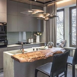 Неиссякаемый источник вдохновения для домашнего уюта: параллельная кухня-гостиная в современном стиле с монолитной раковиной, плоскими фасадами, серыми фасадами, столешницей из бетона, серым фартуком, фартуком из стекла, черной техникой, бетонным полом, островом и серым полом